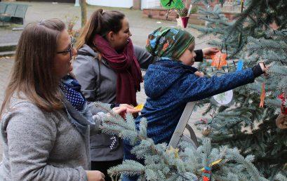 Kinder schmücken den Weihnachtsbaum am Marktplatz